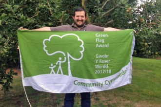Warden of Severn Farm Pond holding the Green Flag Award flag